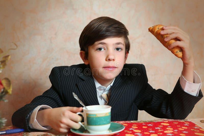 O jogo considerável do menino do preteen com croissan imagina seu um carneiro foto de stock