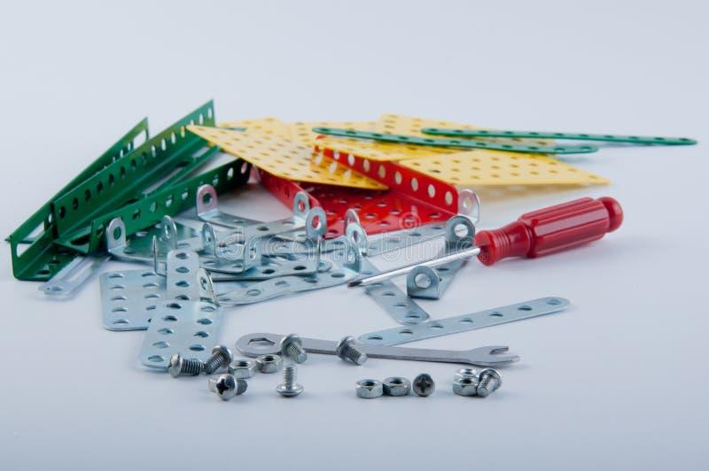 O jogo consiste em ferramentas diferentes e as partes metálicas do construcnor colocam no fundo branco imagem de stock