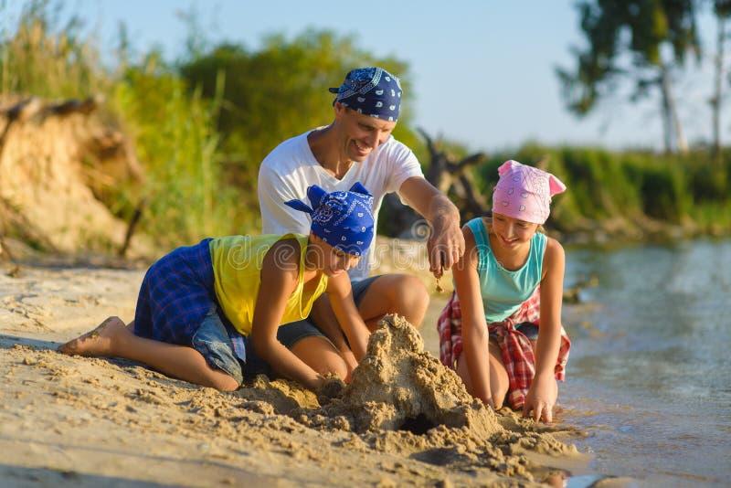 O jogo da família e constrói um castelo da areia na praia Feriado e conceito do curso imagem de stock