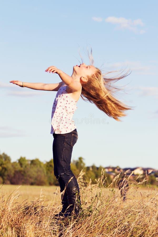 O jogo da menina dirige para trás no vento imagens de stock