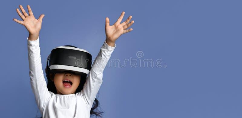 O jogo da realidade virtual da brincadeira da criança da moça veste vidros do vr e explora a realidade alternativa Espaço do Cybe fotos de stock
