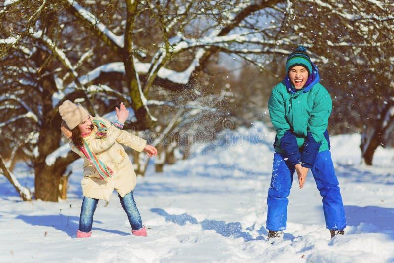 O jogo de crianças na criança nevado da floresta caçoa fora no inverno Amigos que jogam na neve Férias do Natal para a família imagens de stock royalty free