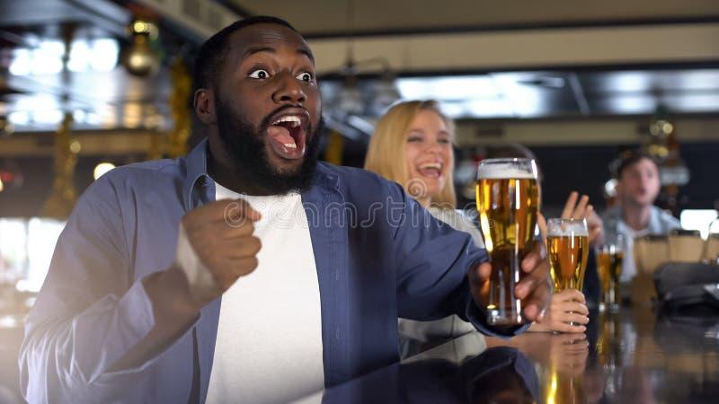 O jogo de observação do suporte preto extremamente emocional e guardar o vidro de cerveja, relaxam foto de stock