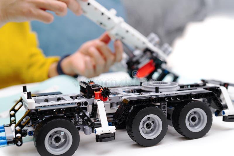 O jogo do conjunto do carro, mulher monta um brinquedo muito complicado e comum do caminhão do carro imagens de stock