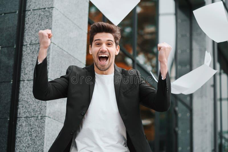 O jogo do homem de negócios forra documentos no ar e comemora o sucesso no fundo do prédio de escritórios Liberdade, bem sucedida imagens de stock