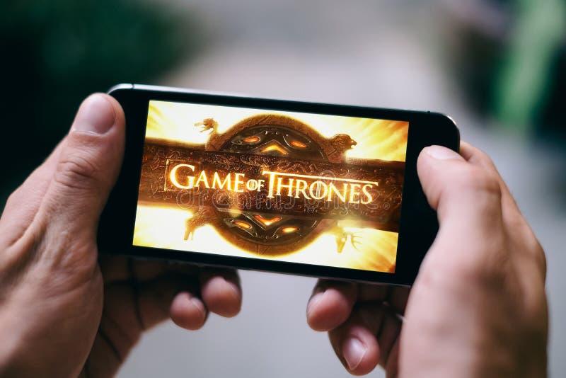 O jogo do logotipo ou do ícone da série de televisão dos tronos é indicado na tela do smartphone imagens de stock