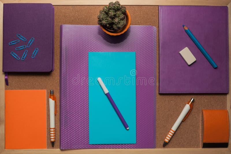 O jogo dos artigos de papelaria está no corkboard imagem de stock