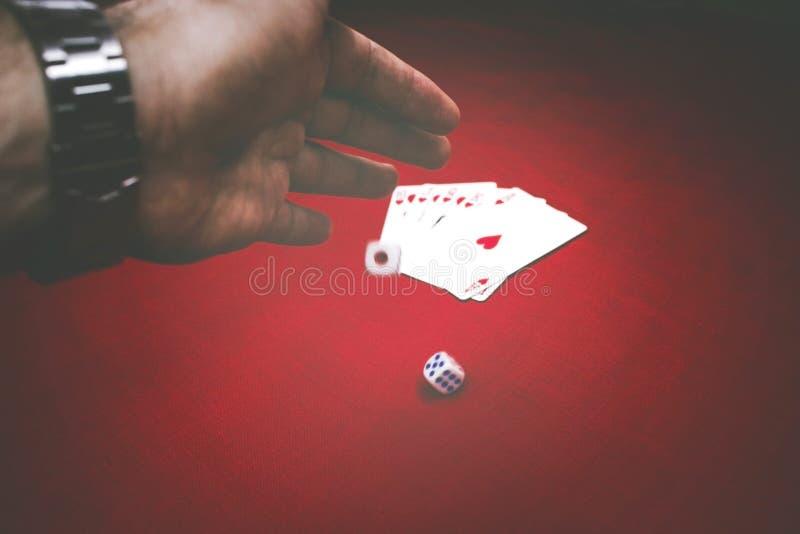 O jogo masculino da mão corta na tabela vermelha com cartões do pôquer fotografia de stock royalty free