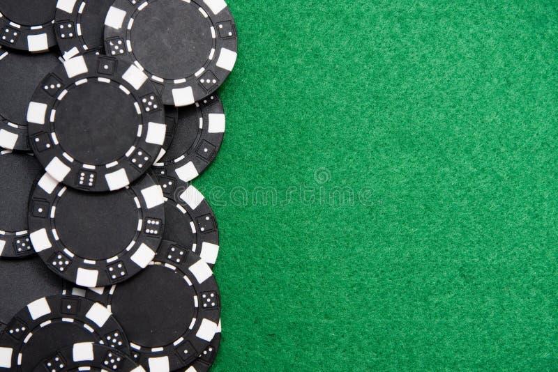 O jogo preto lasca-se no fundo de feltro do verde com foto de stock royalty free