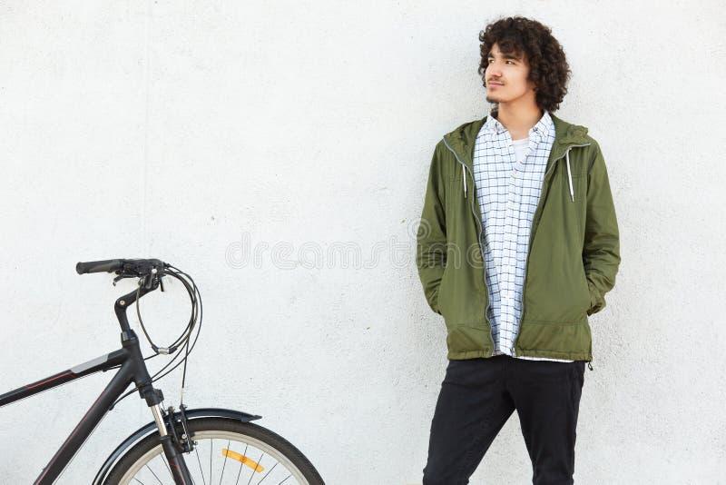 O jovem à moda pensativo com penteado encaracolado, veste o revestimento verde, mantém as mãos no bolso, tem o olhar contemplativ foto de stock royalty free