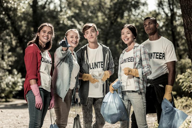 O jovem ativo oferece-se guardando sacos de lixo com lixo após ter limpado a floresta foto de stock royalty free