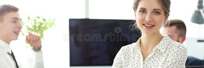 O jovem e belo funcionário sorrindo no escritório olhando à câmera foto de stock