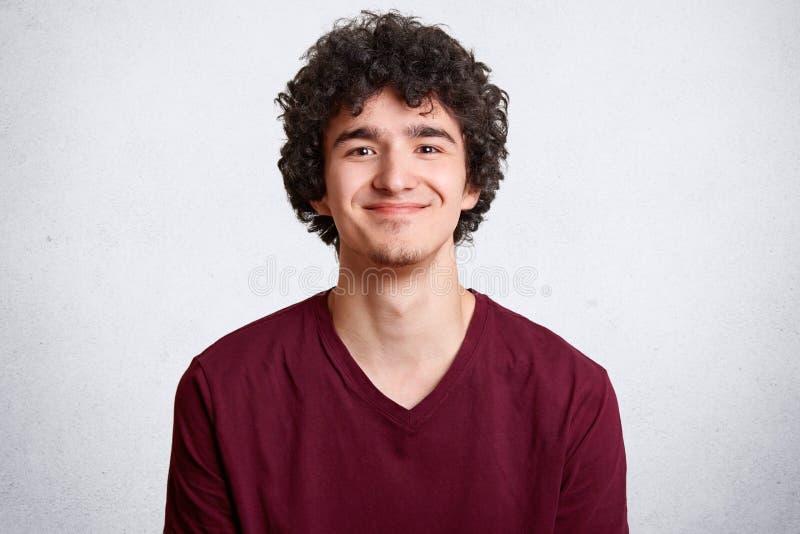O jovem masculino positivo com cabelo encaracolado, olhares alegremente na câmera, tem o sorriso delicado, vestido no equipamento imagem de stock royalty free
