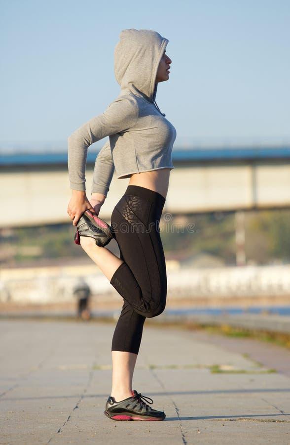O jovem moderno ostenta a mulher que estica os músculos do pé foto de stock royalty free