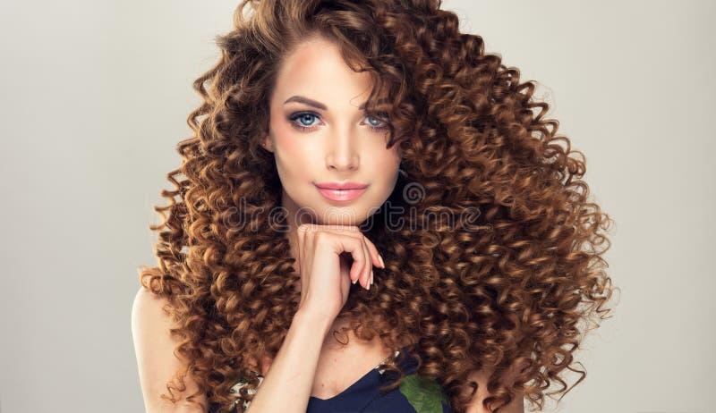 O jovem, mulher de cabelo com denso, elástico do marrom ondula em um penteado imagens de stock
