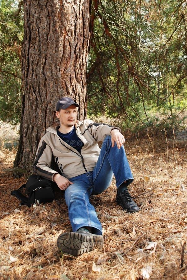 O jovem o homem tem um descanso sob uma árvore fotografia de stock royalty free