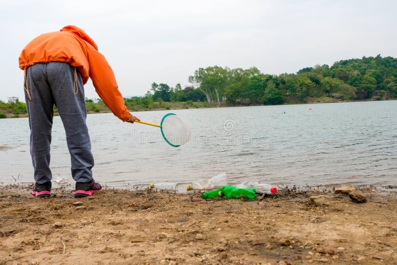 O jovem oferece-se com os sacos de lixo que limpam a área na praia suja do lago, conceito voluntário imagens de stock