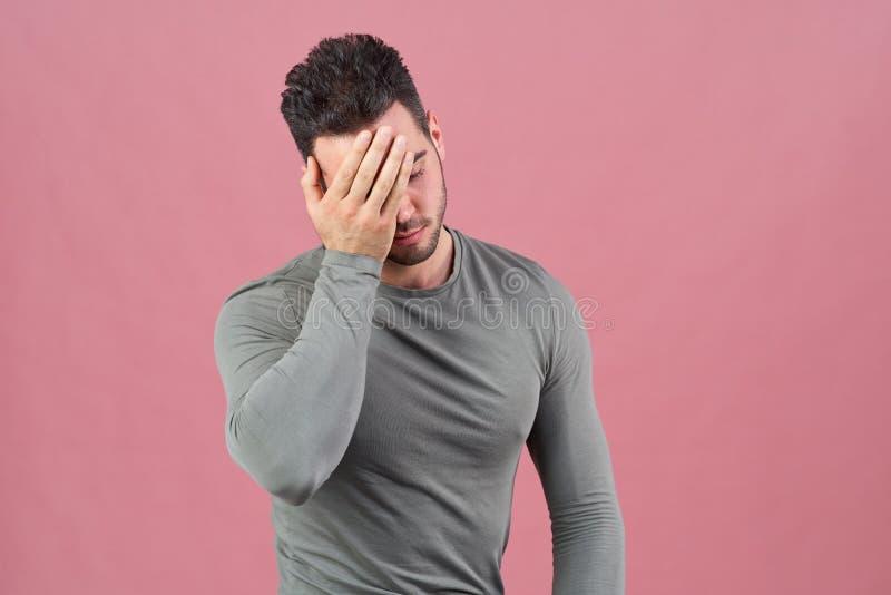 O jovem ostenta imprensas do indivíduo sua palma para enfrentar como um sinal da vergonha, da falha, e da dor de cabeça Emoções,  foto de stock