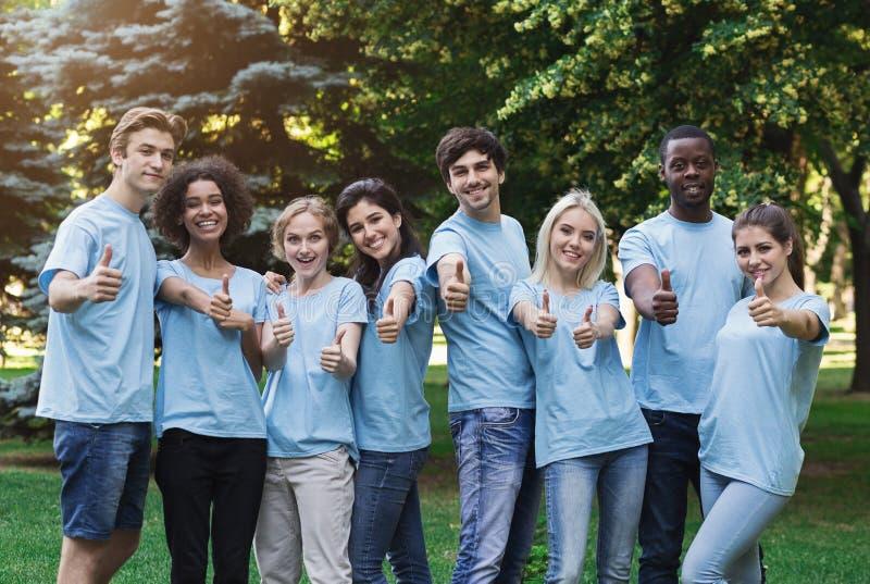 O jovem seguro oferece-se gesticulando os polegares acima no parque fotografia de stock royalty free