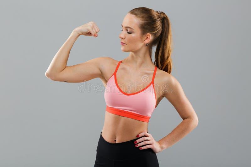O jovem surpreendente ostenta a mulher que mostra o bíceps imagem de stock royalty free