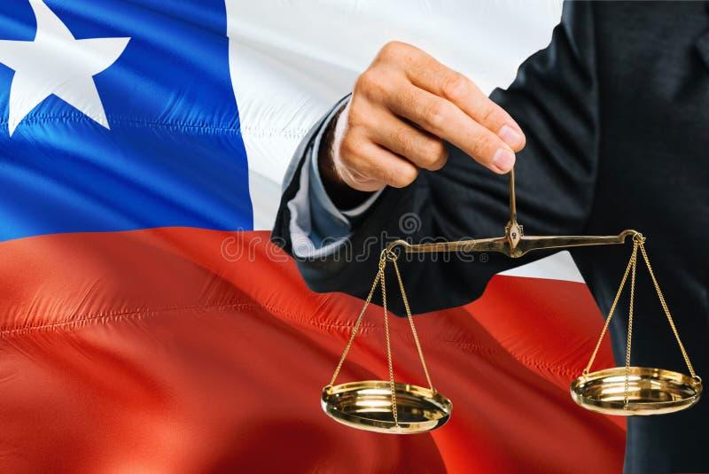 O juiz chileno está guardando escalas douradas de justiça com fundo de ondulação da bandeira do Chile Tema da igualdade e conceit foto de stock royalty free