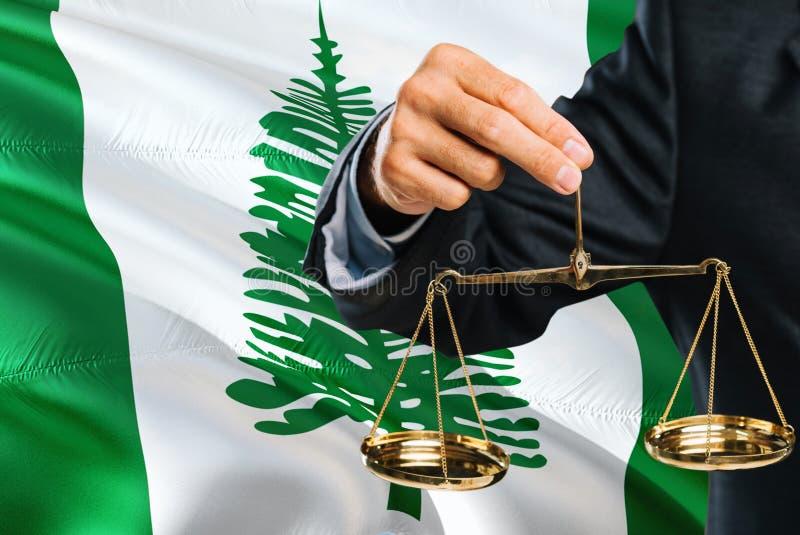 O juiz está guardando escalas douradas de justiça com fundo de ondulação da bandeira de Ilhas Norfolk Tema da igualdade e conceit foto de stock