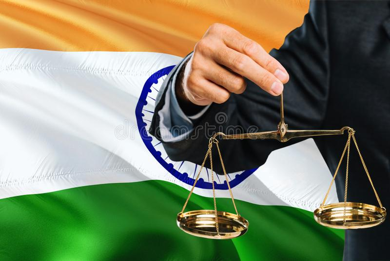 O juiz indiano está guardando escalas douradas de justiça com fundo de ondulação da bandeira da Índia Tema da igualdade e conceit foto de stock royalty free