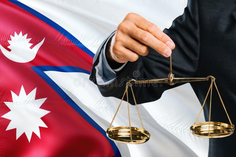 O juiz nepalês está guardando escalas douradas de justiça com fundo de ondulação da bandeira de Nepal Tema da igualdade e conceit fotos de stock
