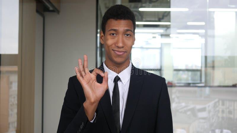 O.k. Teken door de Zwarte Mens in Kostuum in Bureau stock fotografie