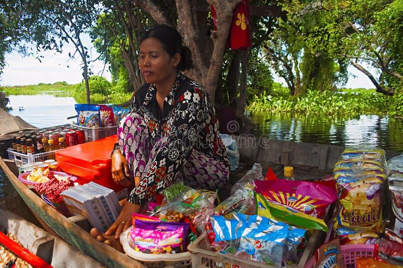 O KAMPONG PHLUK, CAMBOJA, em outubro de 2016, mulher vende artigos dos confeitos no barco no mercado de flutuação foto de stock royalty free