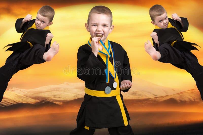 O karaté do rapaz pequeno mostra as técnicas da arte marcial japonesa do karaté no por do sol O karaté é o vencedor com medalhas foto de stock royalty free