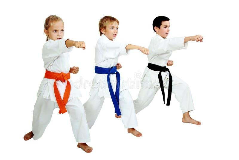 O karateka três no quimono bateu um braço do perfurador imagens de stock royalty free