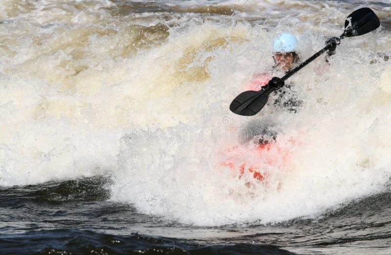 O Kayaker e a onda transformam-se uma imagem de stock