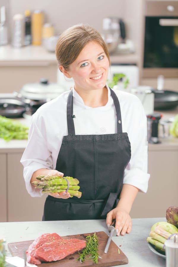 O kitchener fêmea de sorriso no uniforme está estando na cozinha no restaurante fotografia de stock