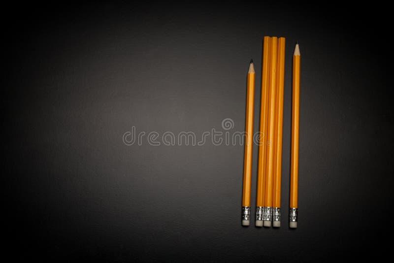 O lápis cinco amarelo está na tabela/fundo pretos Há o lápis apontado dois, três não usados Dia da qualidade do mundo imagem de stock