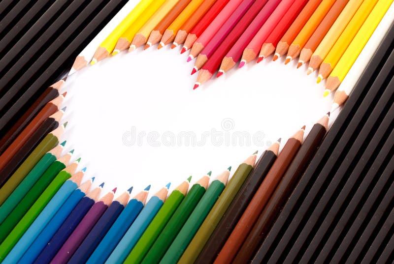 O lápis pastel colorido arranja na forma do coração imagem de stock royalty free