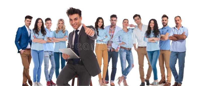 O líder da equipa assentado do homem de negócios com tabuleta faz o sinal aprovado fotografia de stock