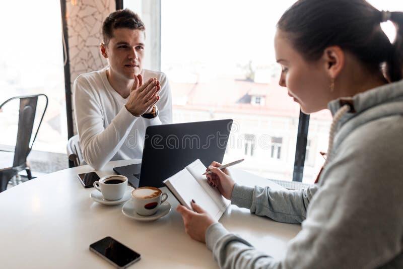 O líder e o proprietário empresarial bem sucedidos conduzem uma reunião de negócios informal em um café A jovem mulher toma notas imagens de stock royalty free