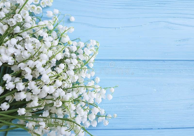 O lírio do vale bonito na mola floral decorativa da celebração de madeira azul floresce cumprimentos fotografia de stock