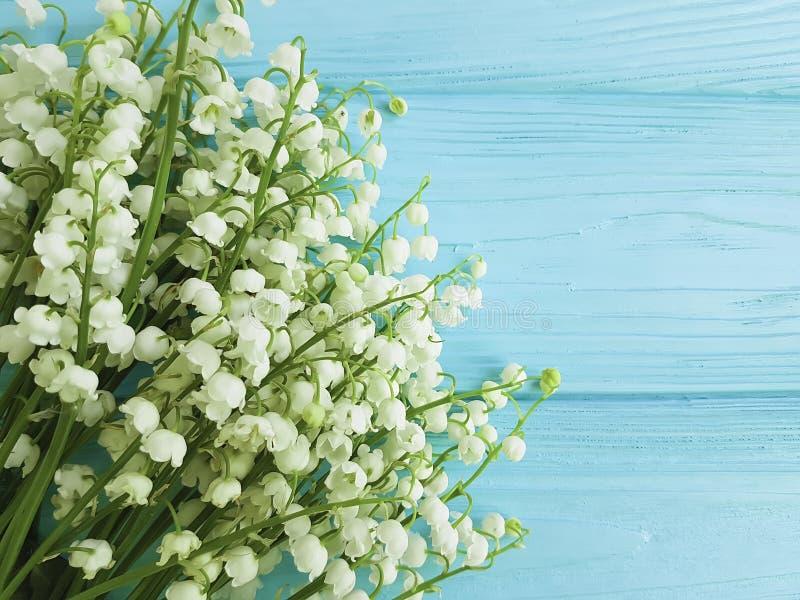 O lírio do vale na mola floral da celebração de madeira azul floresce cumprimentos imagens de stock