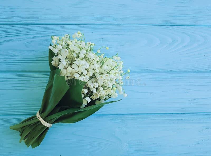 O lírio do vale rústico na mola floral decorativa da celebração rústica de madeira azul floresce cumprimentos imagem de stock