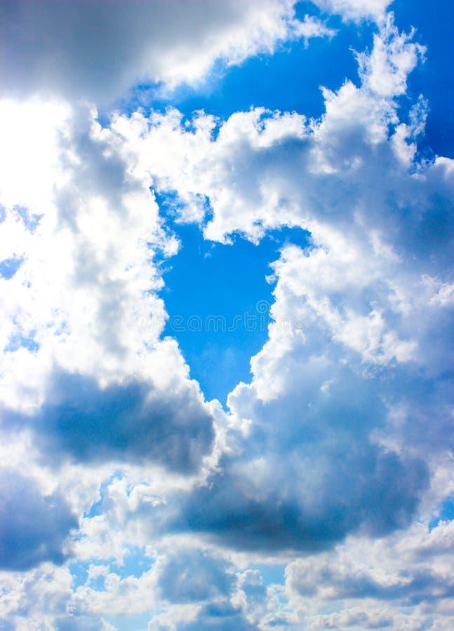 O lúmen do céu azul entre as nuvens brancas na forma de um coração imagens de stock royalty free