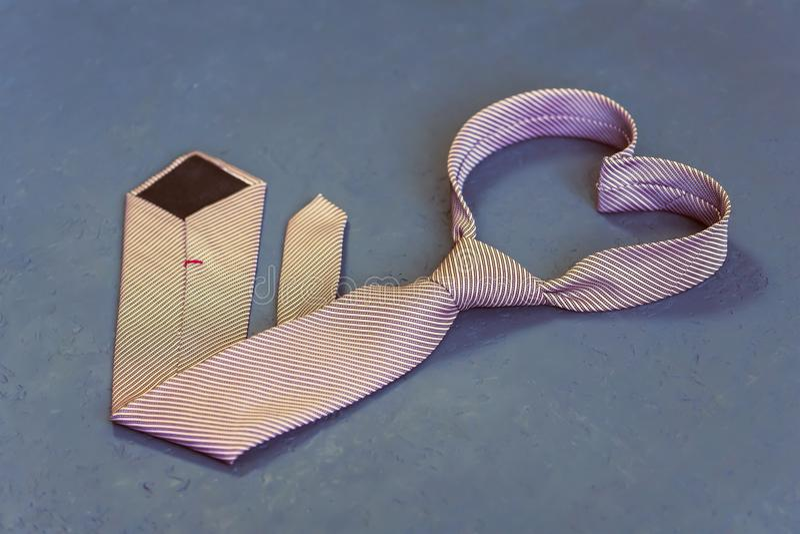 O laço cor-de-rosa é amarrado na forma de um coração em um fundo cinzento fotografia de stock