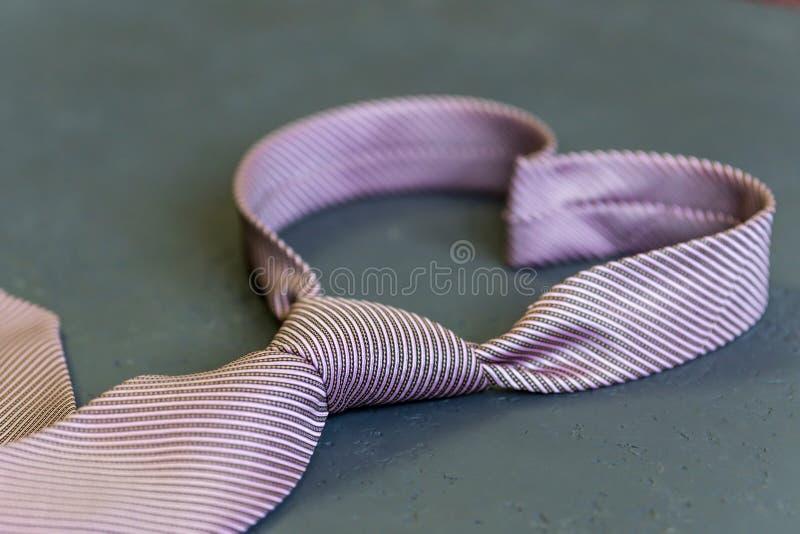 O laço cor-de-rosa é amarrado na forma de um coração em um fundo cinzento T imagens de stock royalty free