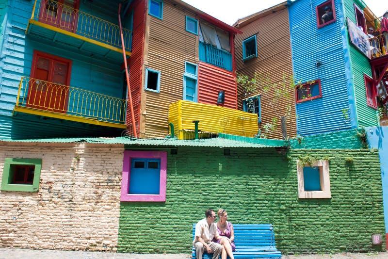O La Boca Buenos Aires, acopla o assento no banco entre paredes e casas coloridas em Caminito fotos de stock
