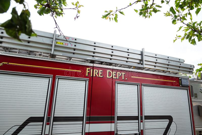 O lado de um carro de bombeiros vermelho com o departamento dos bombeiros escrito no lado foto de stock royalty free