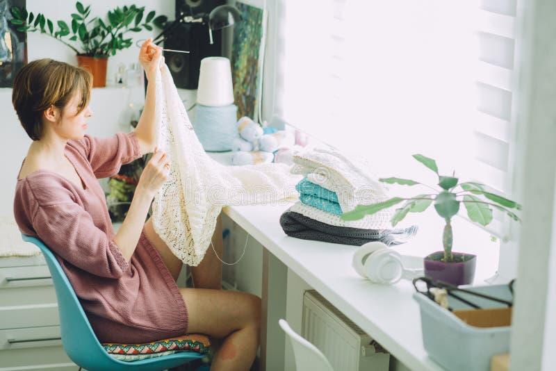 O lado do desenhista da mulher que faz malha o vestido macio com faz crochê no trabalho criativo do freelancer fêmea interior mod imagem de stock royalty free