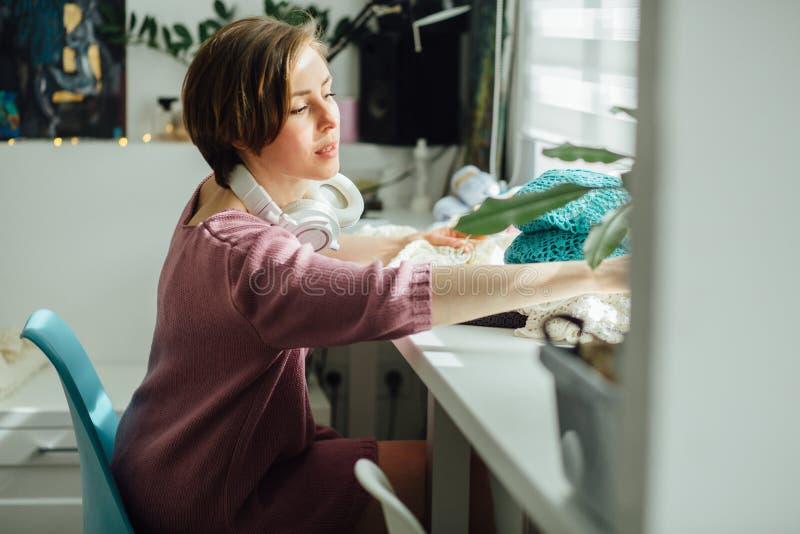 O lado do desenhista da mulher que faz malha o vestido macio com faz crochê no trabalho criativo do freelancer fêmea interior mod imagens de stock