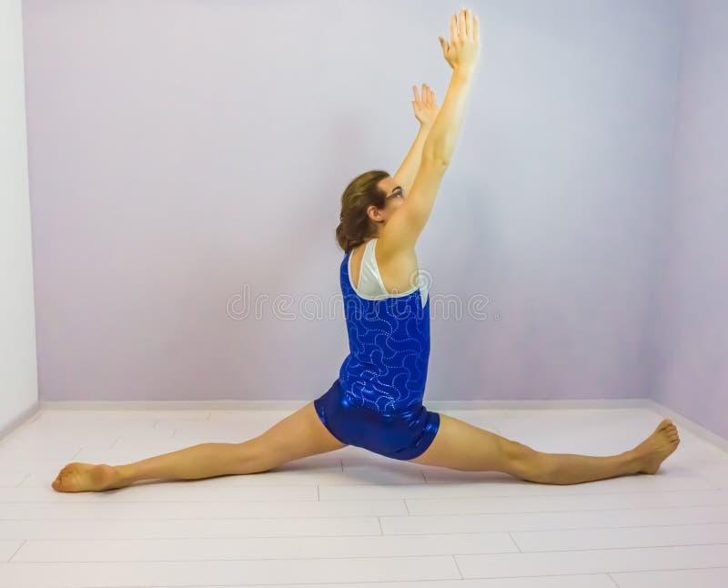 O lado do exercício da flexibilidade da ginástica rachou no assoalho pré-formado por uma menina nova do transgender que veste uma fotos de stock royalty free
