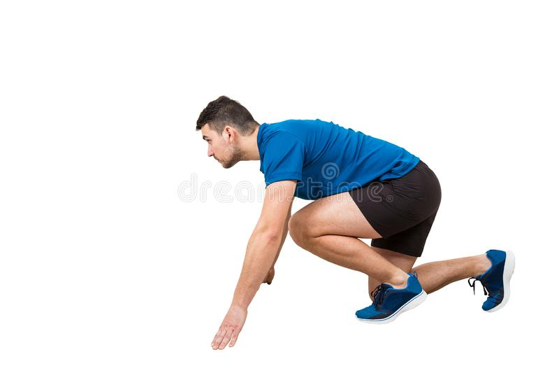 O lado vie o comprimento completo de posição caucasiano determinada do corredor do homem em anticipar da posição de corrida segur foto de stock royalty free